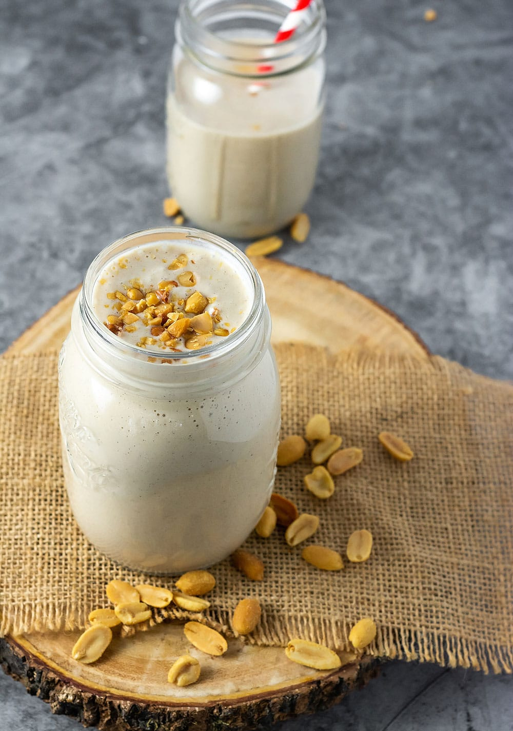 Peanut punch in a glass jar garnished on top with crushed peanuts on a burlap napkin