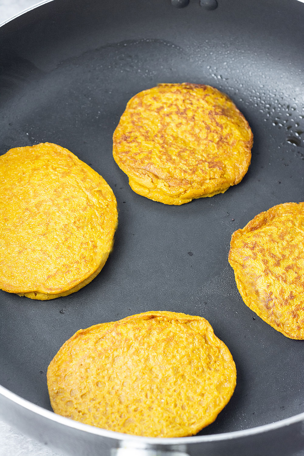 vegan pumpkin pancakes in the skillet being cooked