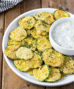 Vegan air-fryer zucchini chips on a white plate topped with a small white bowl with vegan ranch dip on a brown wooden board