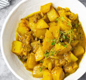 overlay, jamaican chocho/chayote curry in a white bowl