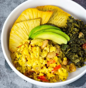 Overlay Ackee and butter beans served in a white bowl with roast breadfruit, callaloo and avocado