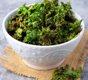 Air fryer kale chips in a white bowl on a burlap napkin on a gray marble background
