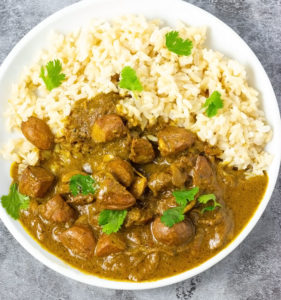 Chataigne curry overlay with rice in a white plate on a grey background
