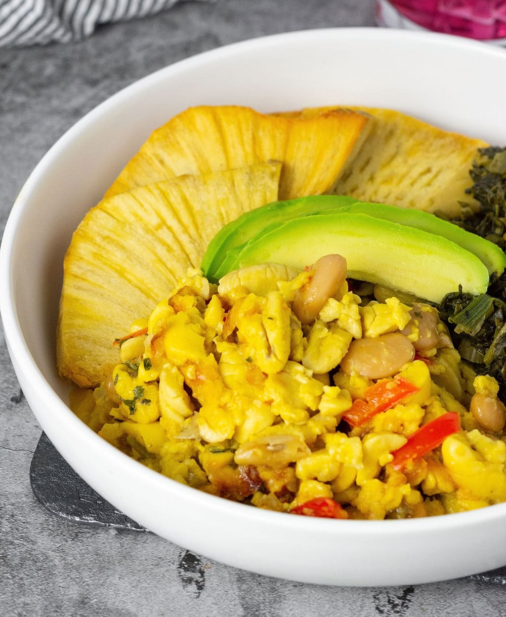 Easy Ackee and butter beans served in a white bowl with roast breadfruit, callaloo and avocado