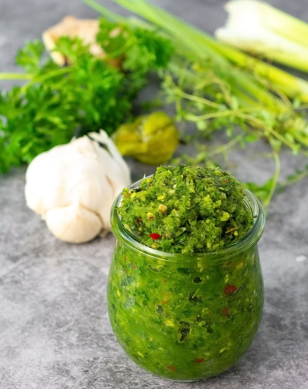green seasoning recipe in a glass jar on a grey marble background with celery, garlic, pepper, ginger in the background