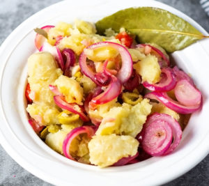 guineos en escabeche overlay green banana red onion pickle in a white bowl on a grey background