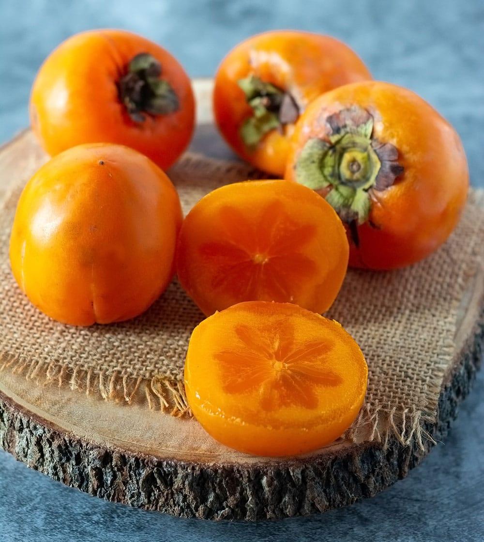 ripe persimmons on cutting board