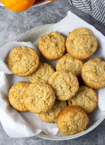 Overlay of vegan persimmon banana muffins in a bowl on a grey marbled background