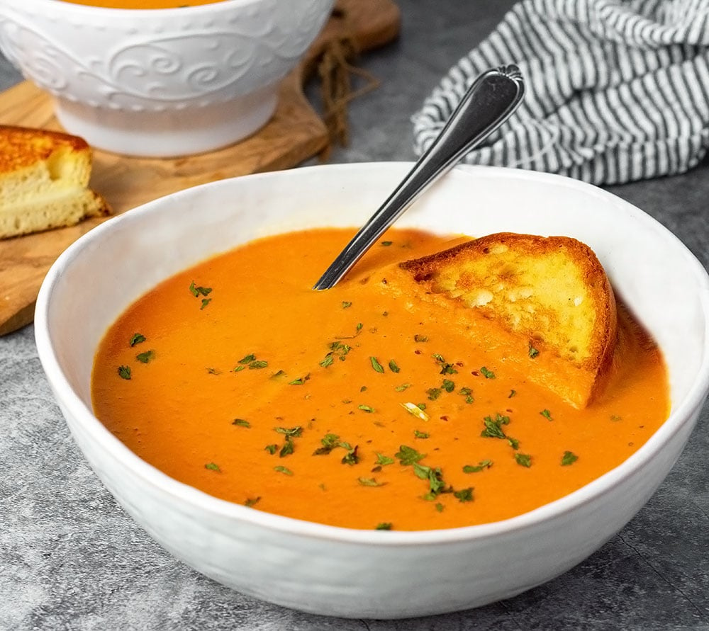 Vegan tomato soup in white bowls with grill cheese sandwich, in the background cutting board with soup and sandwich on a grey background