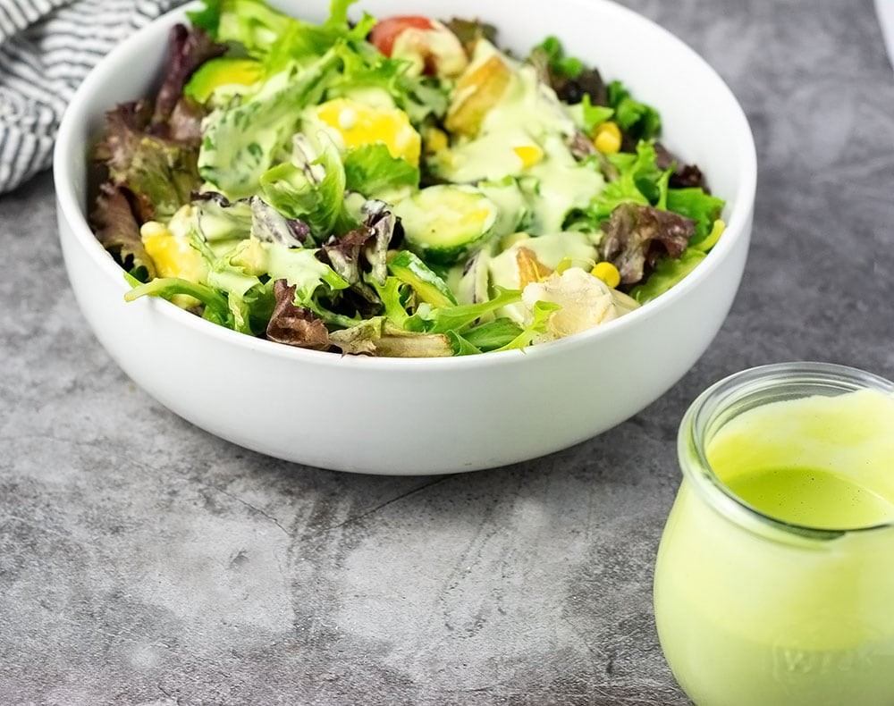 cilantro lime salad dressing in the front of a white bowl of salad with dressing poured on top