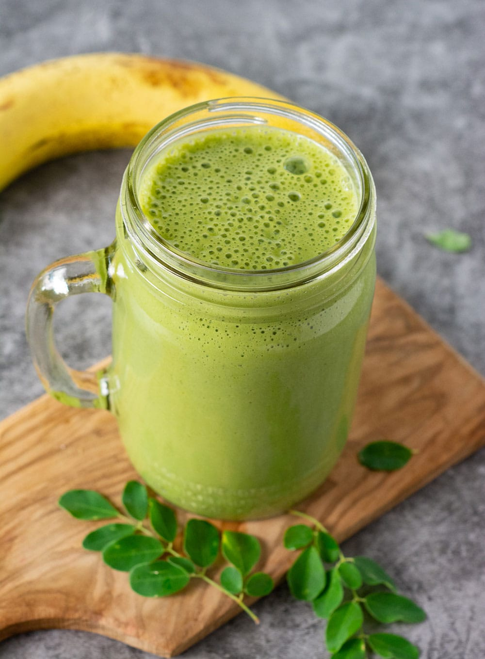 Overlay of moringa smoothie in a glass jar on a wooden cutting board, with moringa leaves and ripe banana
