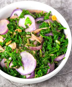 Green sauteed radish leaves and slices of purple sauteed radishes in a white bowl over a grey marbled background
