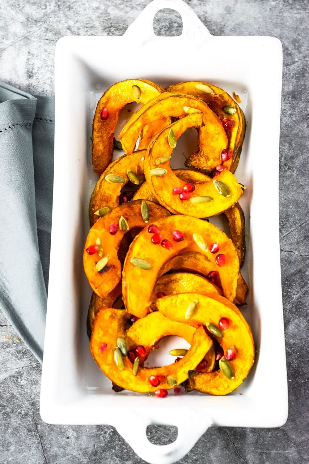Roasted kabocha squash on a white serving dish garnished with pomegranate and pumpkin seeds, with a grey napkin on a grey marbled board.