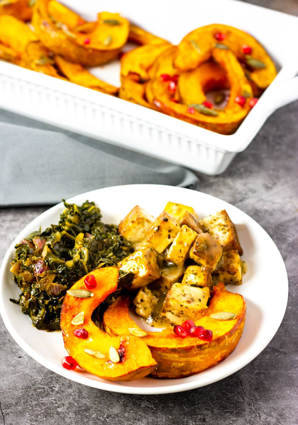 roasted kabocha squash in a white plate with collard greens and smothered tofu on a marbled background