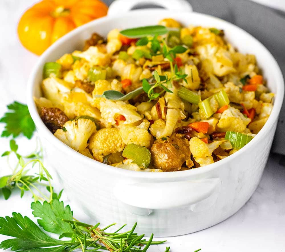 Vegan Cauliflower Stuffing, in a white casserole dish on a white marble background with a grey napkin on the side