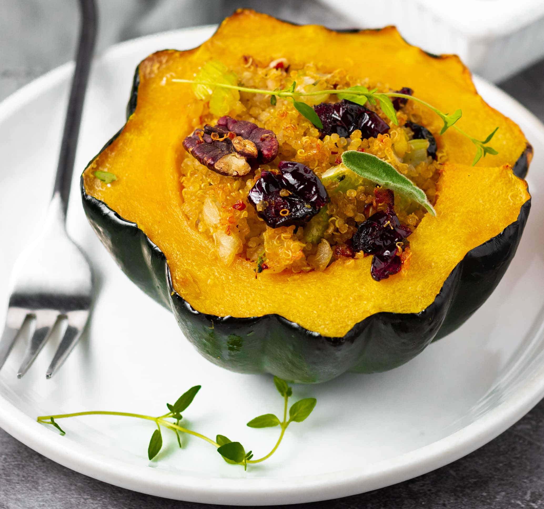Vegan Stuffed acorn squash on a white plate stuffed with quinoa, cranberries, pecans, and sausage with a black fork