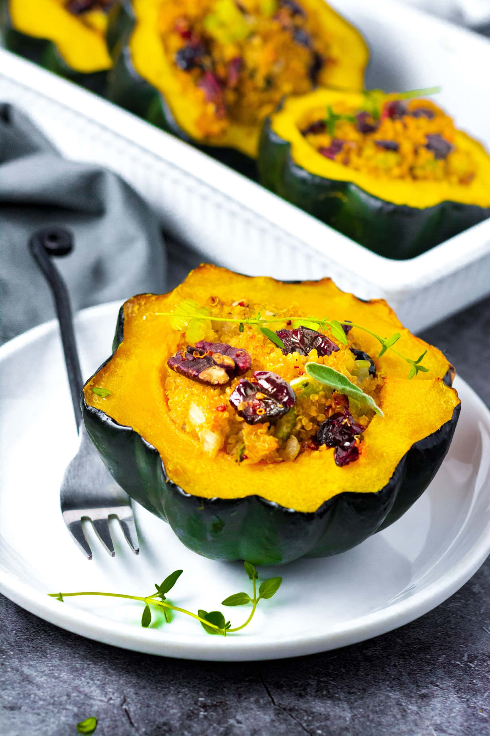 Vegan Stuffed acorn squash on a white plate stuffed with quinoa, cranberries, pecans, and sausage with a black fork with a white casserole dish in the background