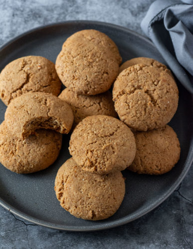 vegan gingerbread cookies on a dark plate, with a grey napkin on a grey marbled background