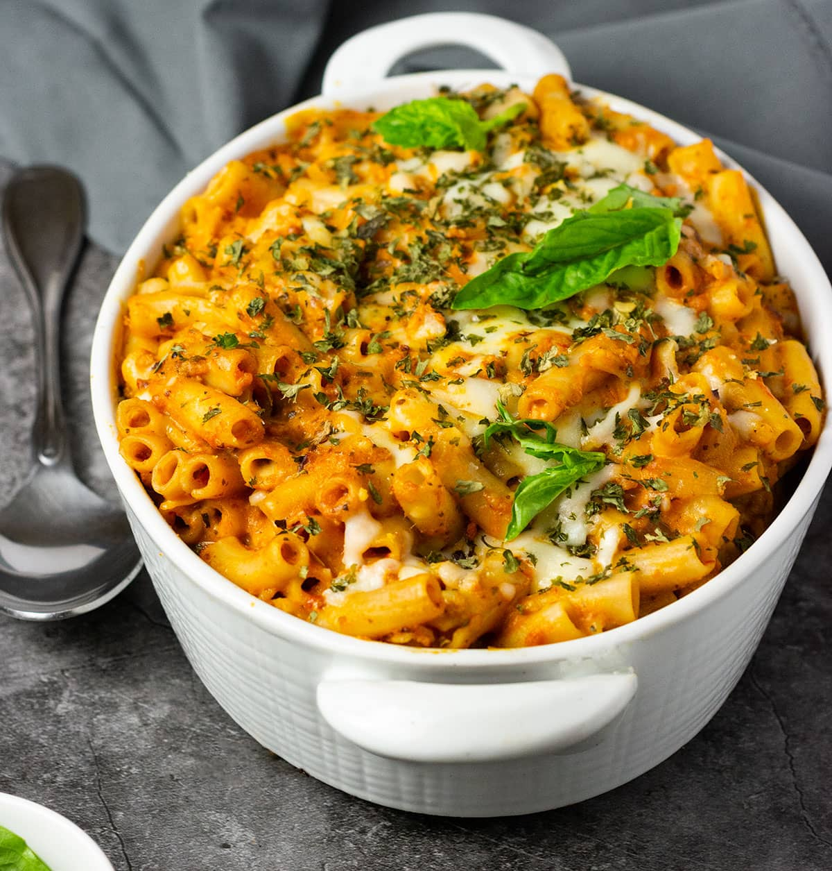 vegan baked ziti straight on image on a grey background in a white pan