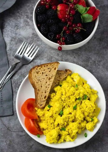 Overlay vegan scrambled tofu with sliced bread and tomato on a white plate with fruit bowl in the background