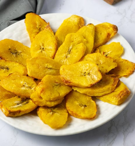 Close up air fryer plantains on a white plate ion a white background