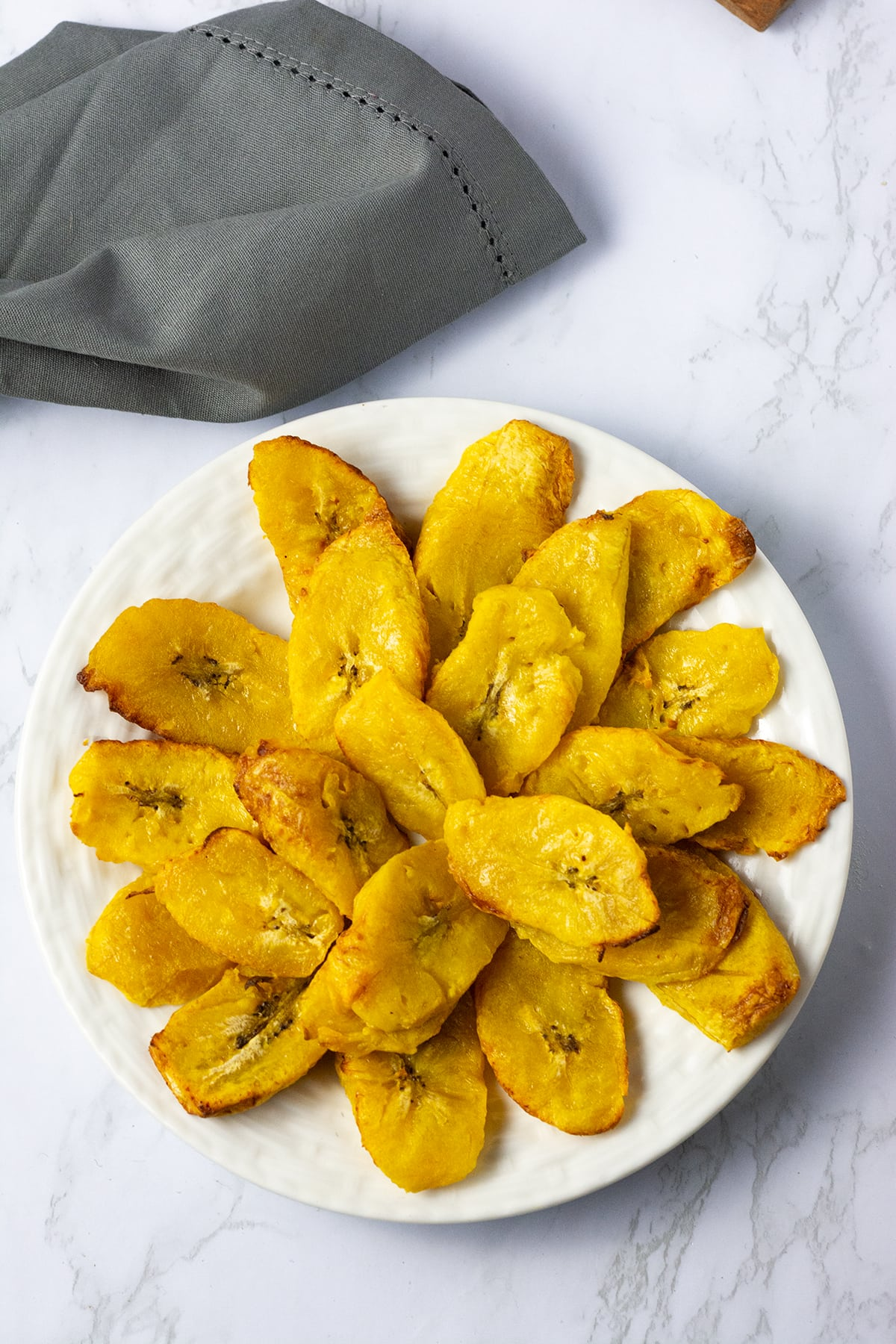 Overlay air fryer plantains on a white plate and white background