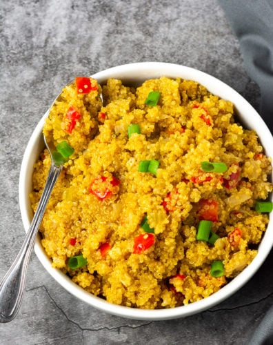 Overlay vegan quinoa pilaf, quinoa cooked with onion, garlic, celery bell pepper and Creole seasoning