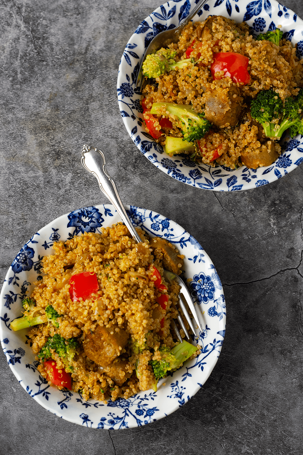 quinoa fried rice overlay in two white and blue floral bowls with two forks on a grey background