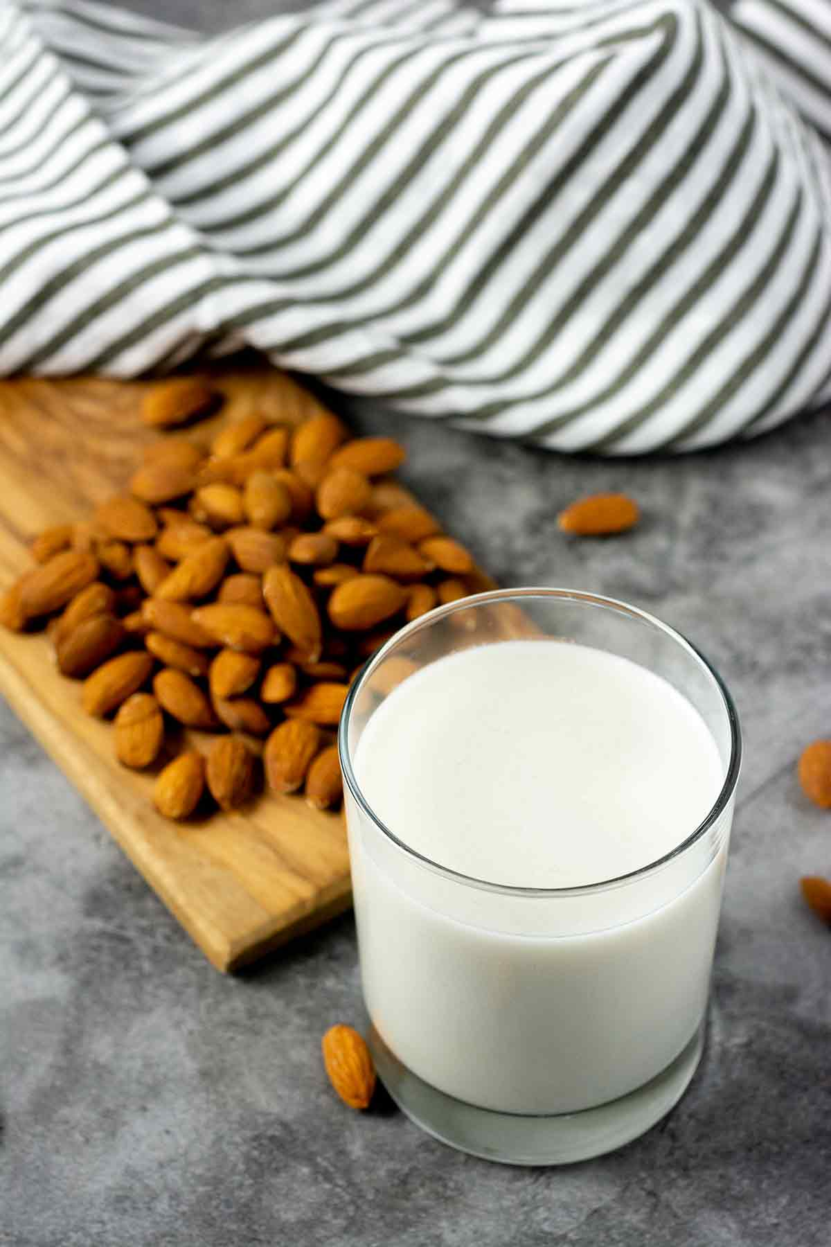 Overlay Almond milk in a glass jar with almonds on a cutting board in the background