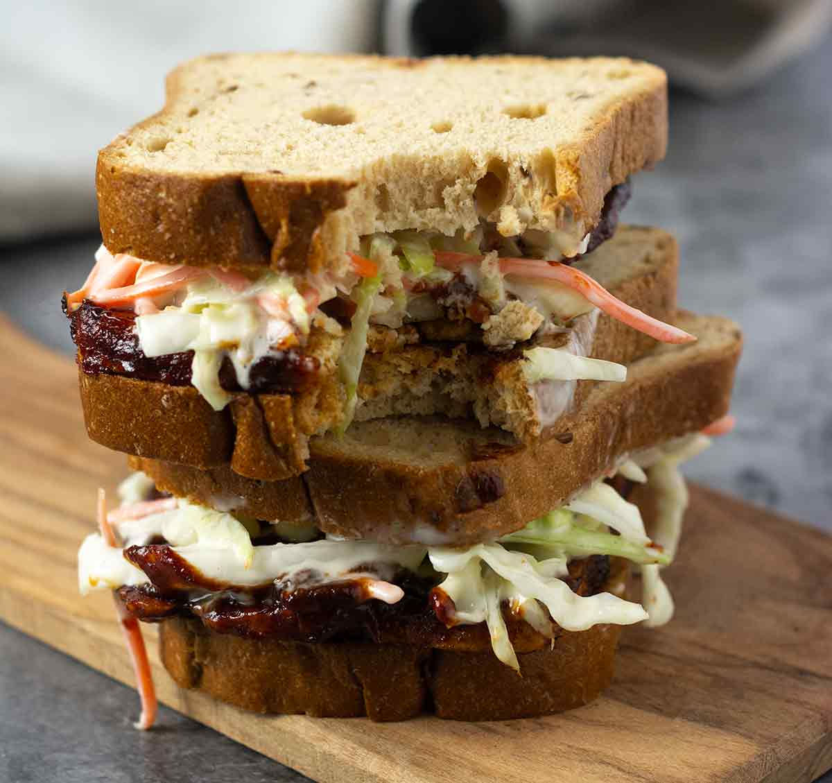 Stacked barbecue tofu sandwiches with the top one having a bite taken