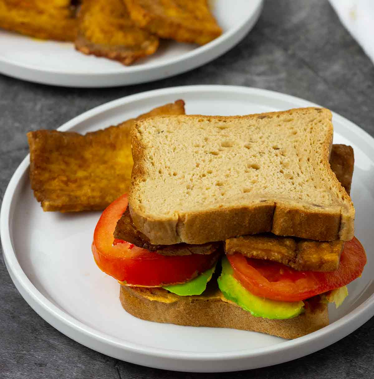 vegan tofu bacon sandwich with tomato, avocado on a white plate on a grey background
