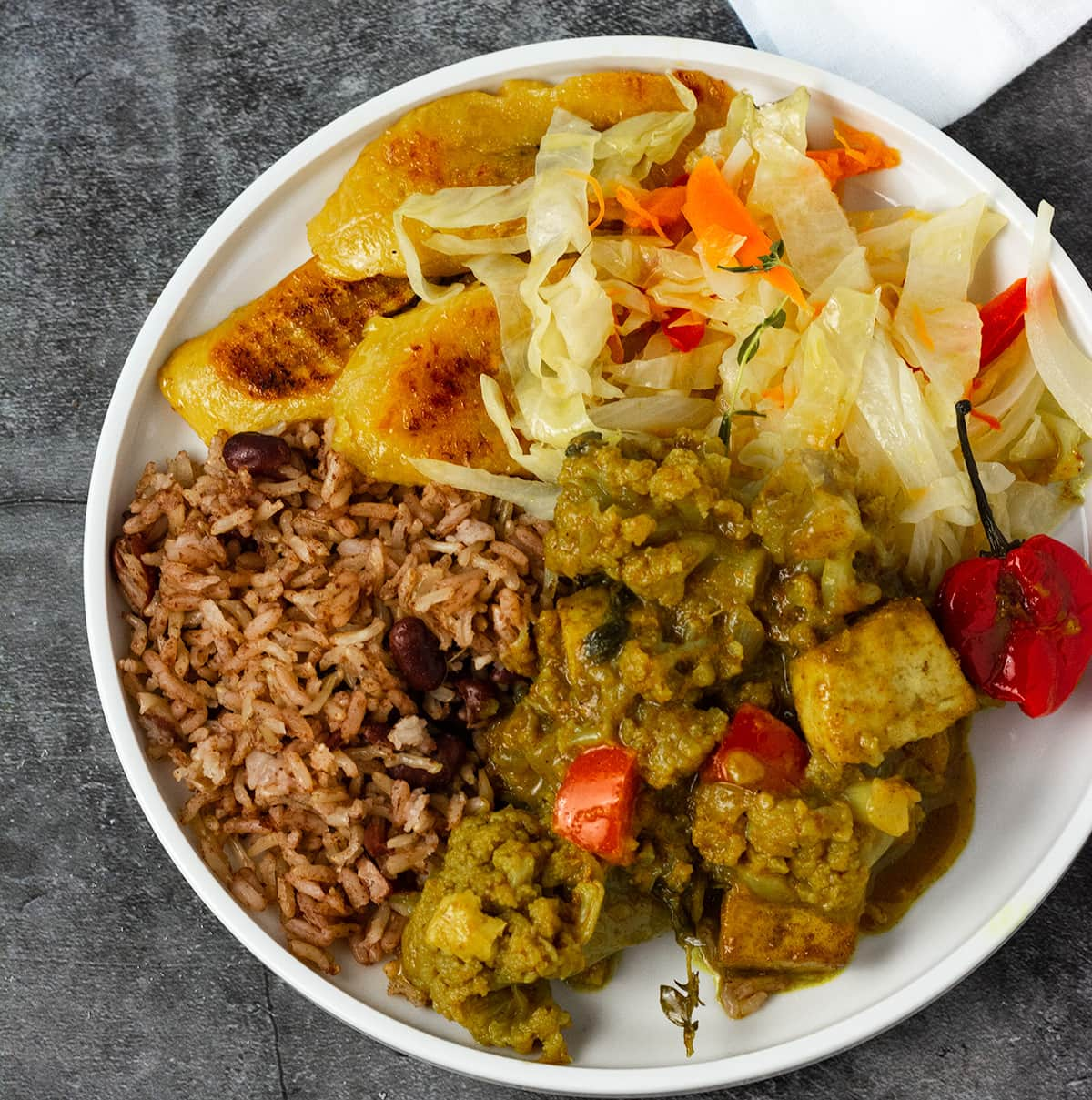 Overlay of curry tofu with cauliflower, steamed cabbage, baked plantains and Jamaican rice and peas on a white plate on a grey background
