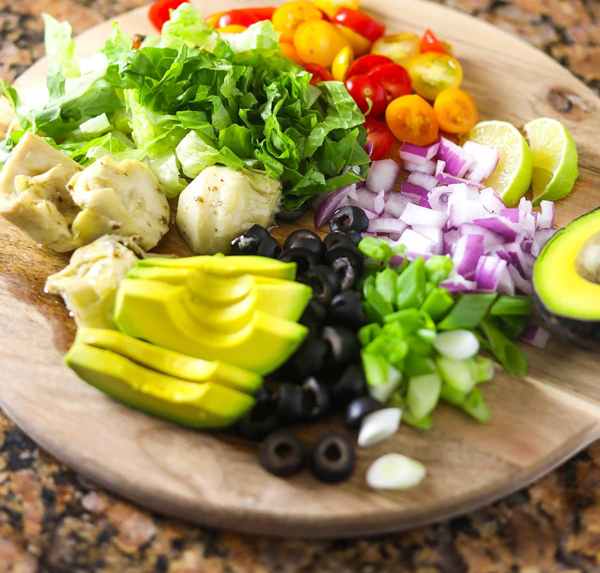 Prepped Cajun tofu salad ingredients on a round wooden cutting board, avocado slices, olives, tomato, lettuce, onion, lime slices