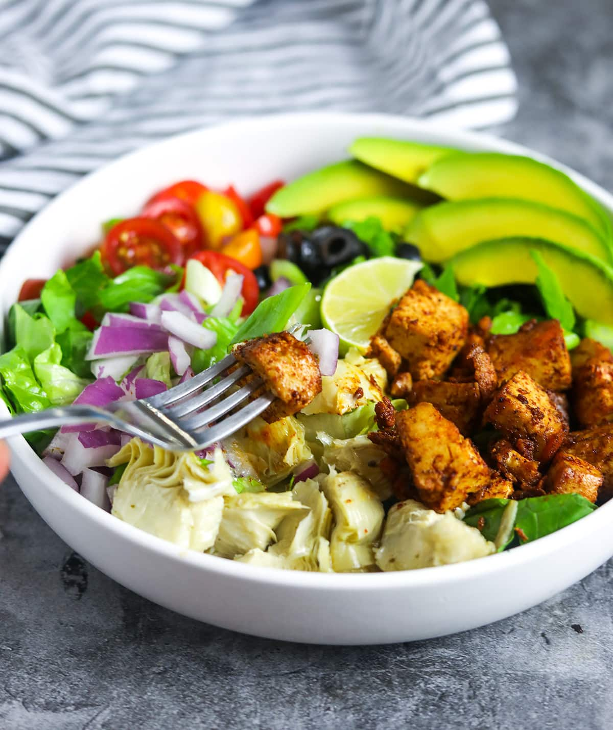 white bowl with cajun tofu salad, fork taking up a bite on a grey background with a black and white stripe napkin