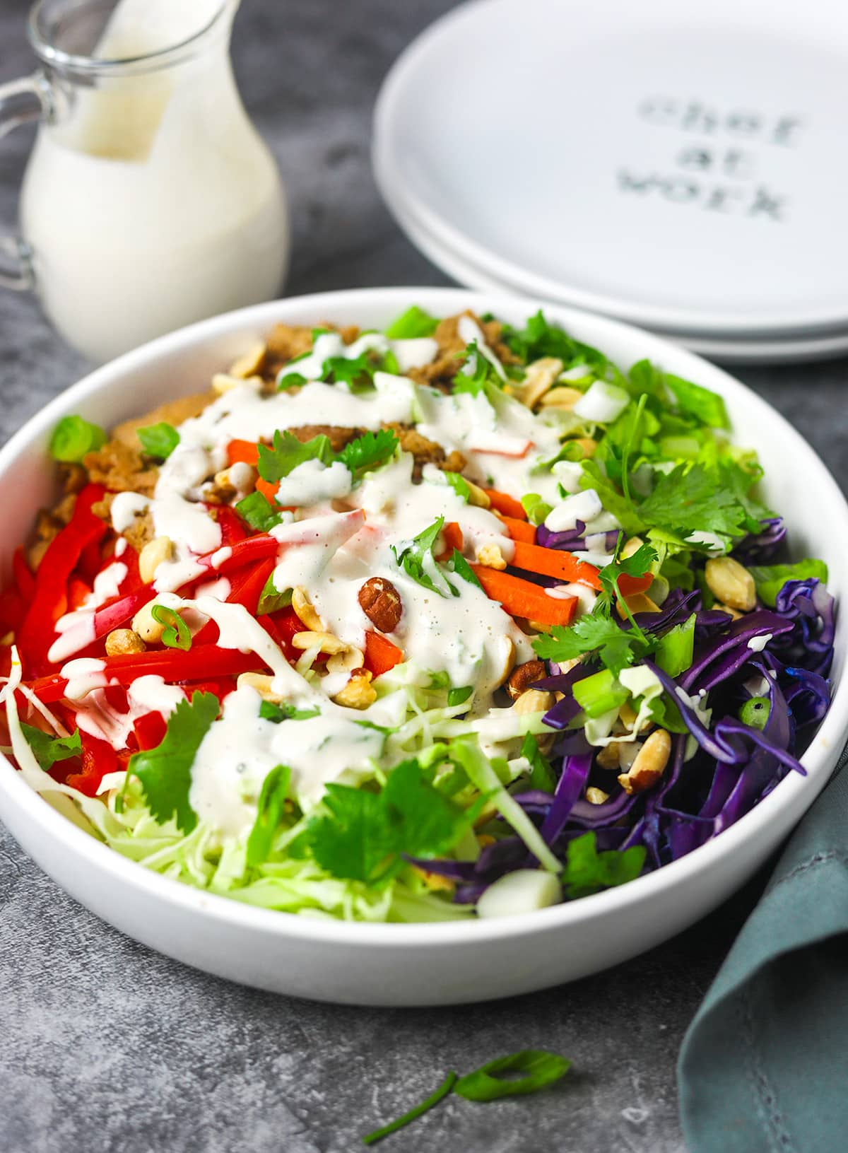 vegan asian salad in a white bowl tossed with creamy vegan asian salad dressing on a grey background with stacked white plates and salad dressing container in the background