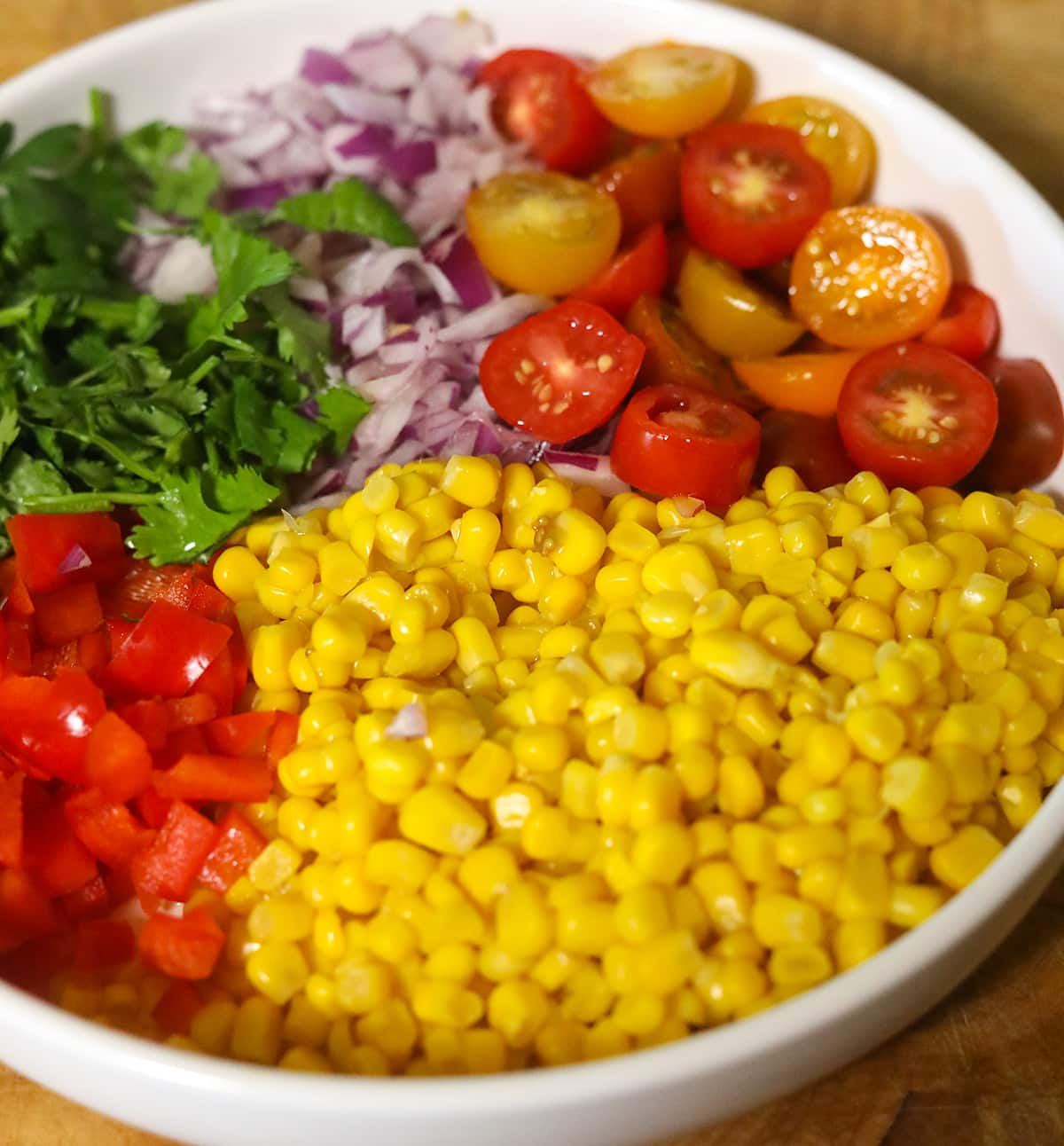 Ingredients for Mexican corn salad in a white bowl