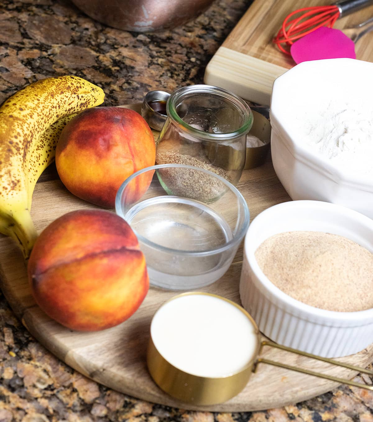 Ingredients for banana peach bread on a round cutting board