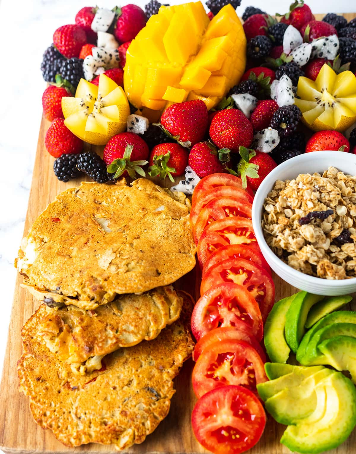 chickpea pancakes on a board, with tomato slices, avocado, granola in a white bowl, strawberries, blackberries, mango, yellow kiwi and dragon fruit