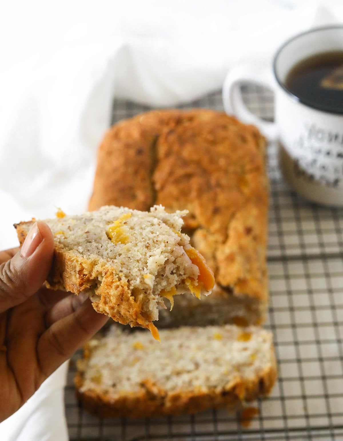 Vegan peach banana bread on a wire rack with two slices, hold one slice in hand on a white background, white napkin and white mug with tea