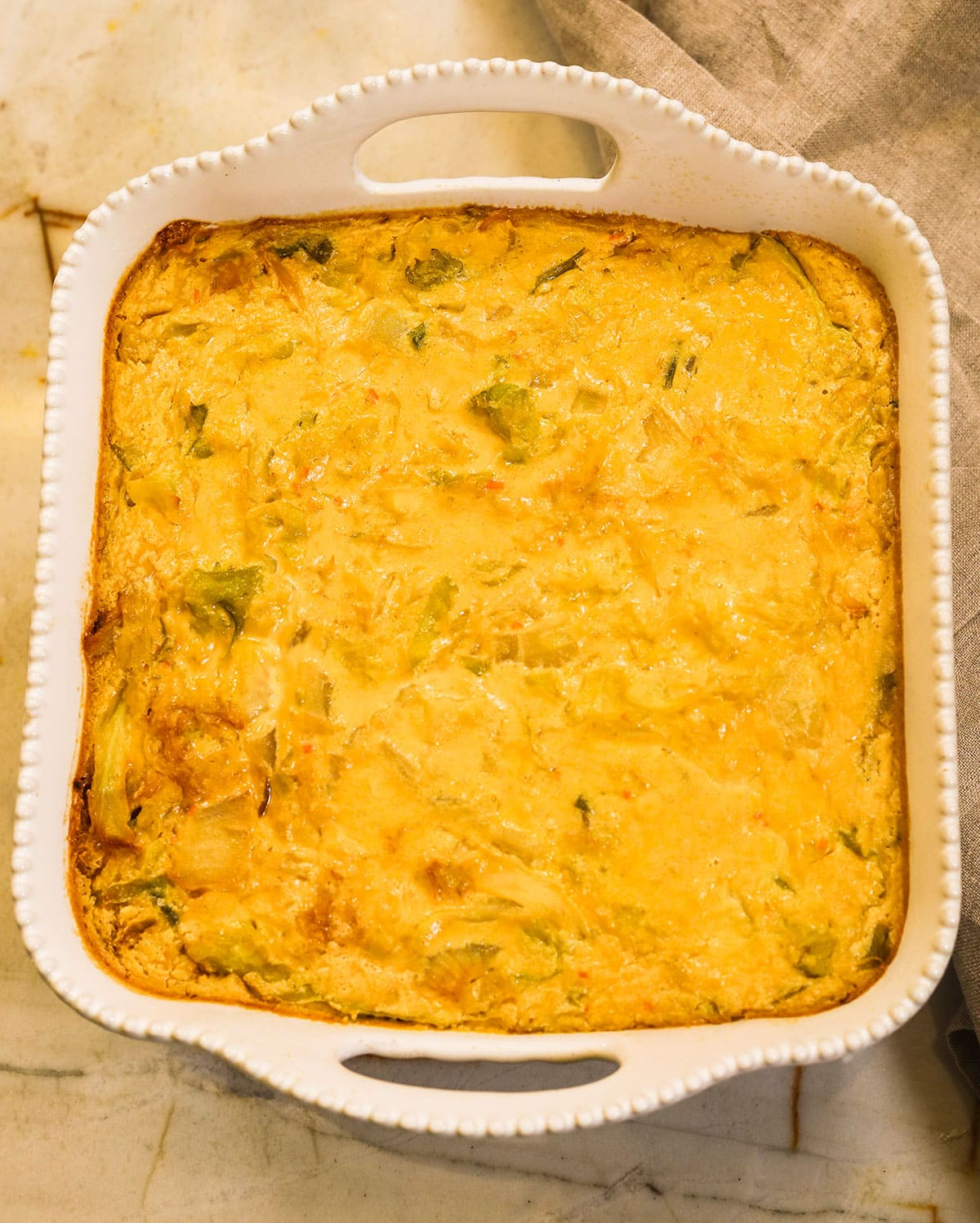 overlay vegan cabbage casserole in a while casserole pan on a marble beige background