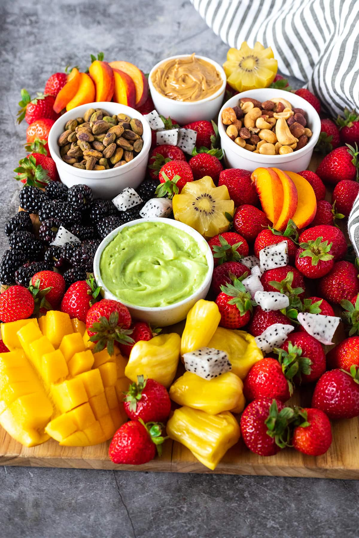 vegan key like dip on a cutting board with fruits like mango, peach, strawberries, nuts