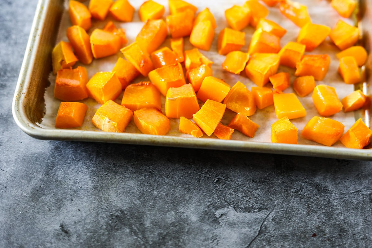 roasted butternut squash overlay on a baking tray