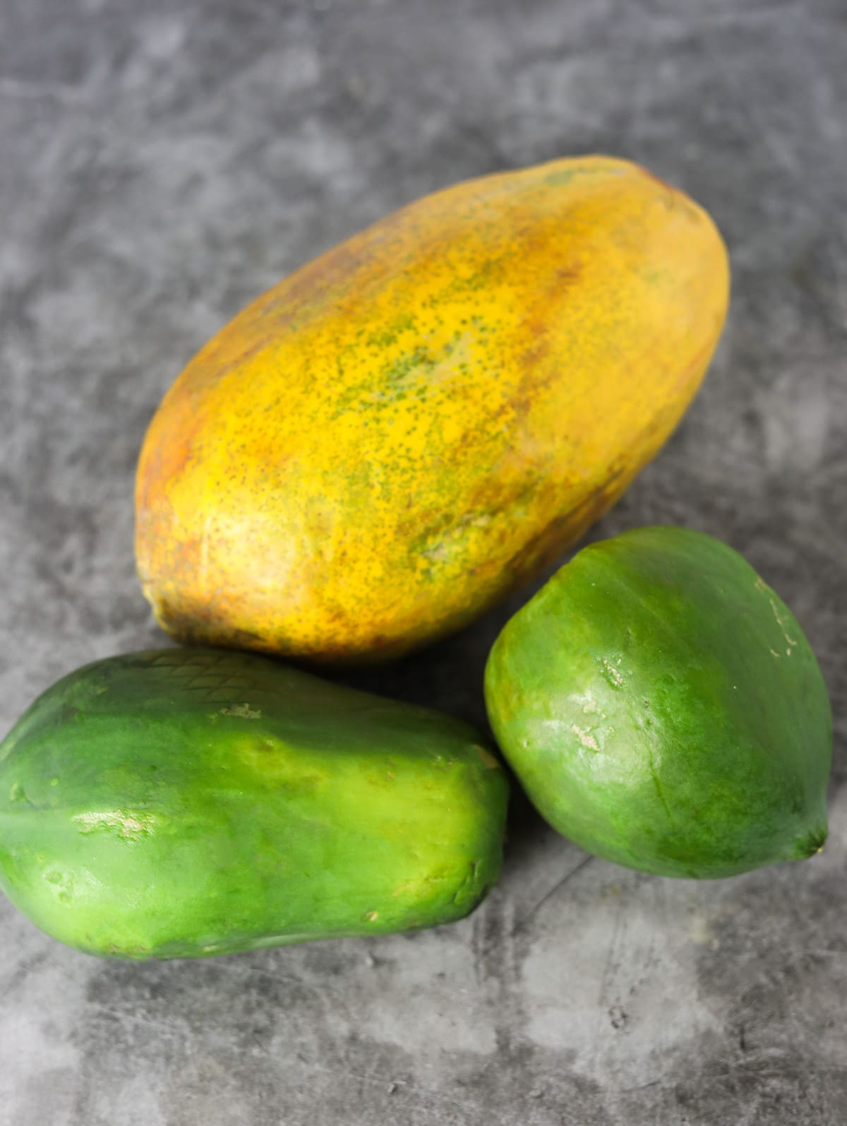 3 papayas, one ripe and 2 green ones