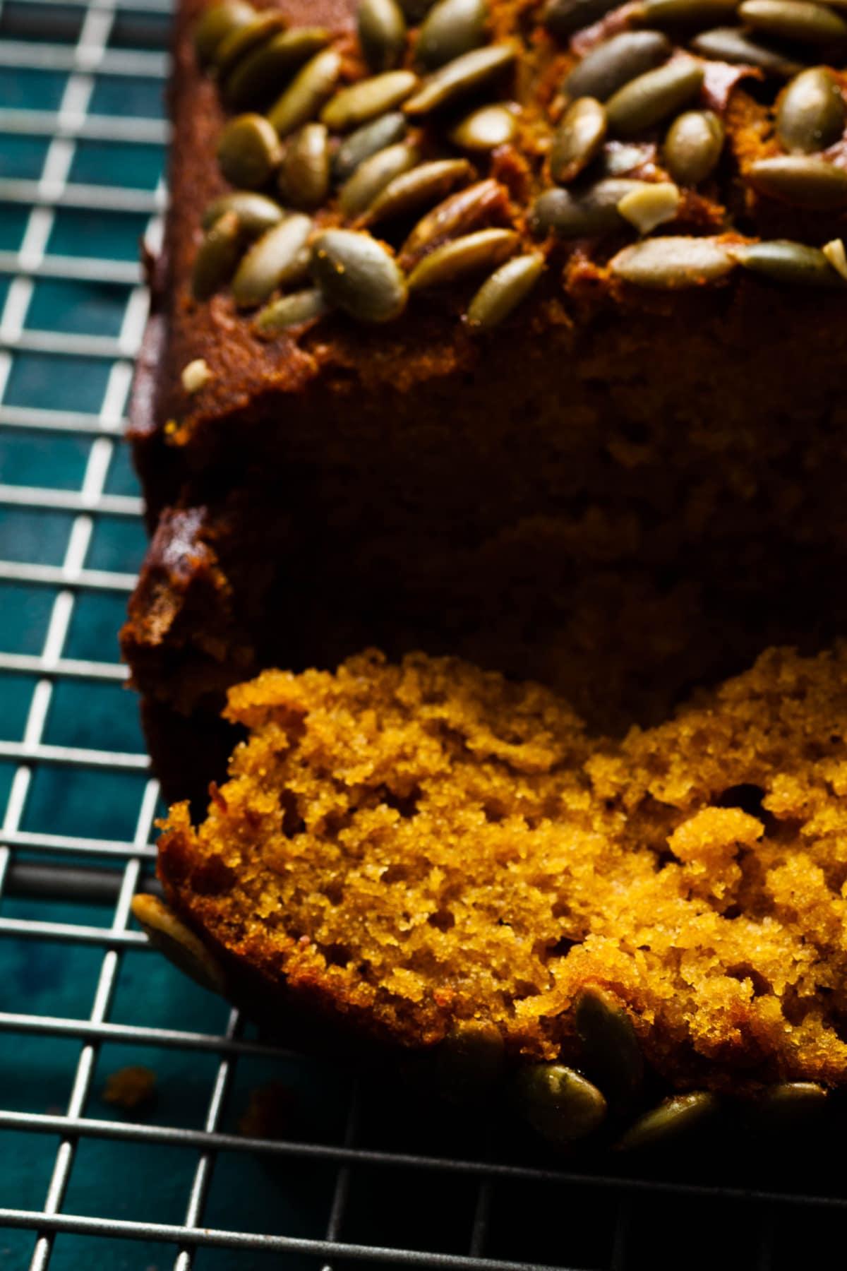 vegan pumpkin bread on cooling rack bread sliced