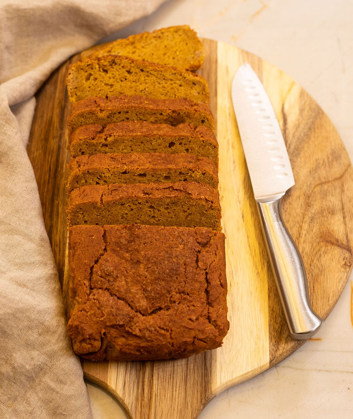 gluten-free pumpkin bread overly, bread cut into slices on a cutting board with a knife on the side
