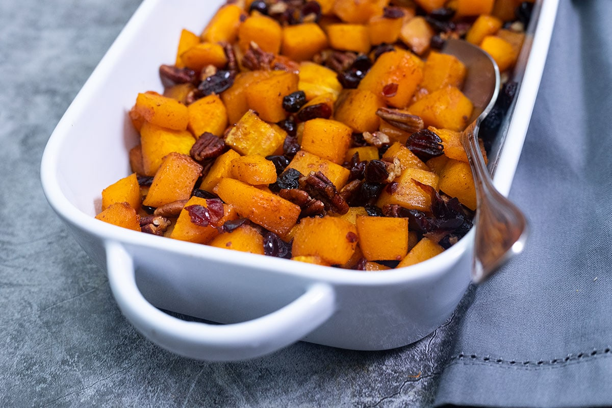 close up of maple roasted butternut squash cubes with cranberries and pecans
