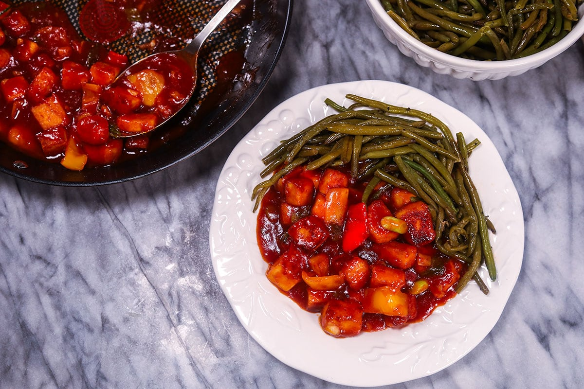 wide angle view of sweet and sour tofu with green beans on a white plate in the middle