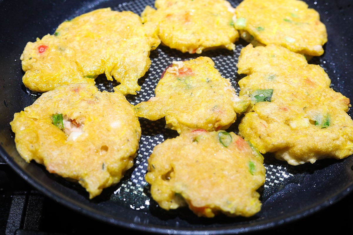 Plantain fritters cooking in a large black skillet