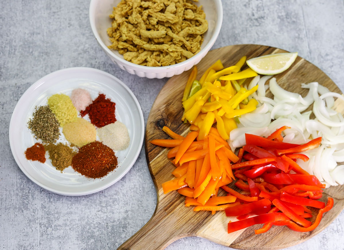 Ingredients for veggie fajita, onion, bell pepper, soy curls, spices and herb on a cutting board, white plate and bowl on a grey concrete background