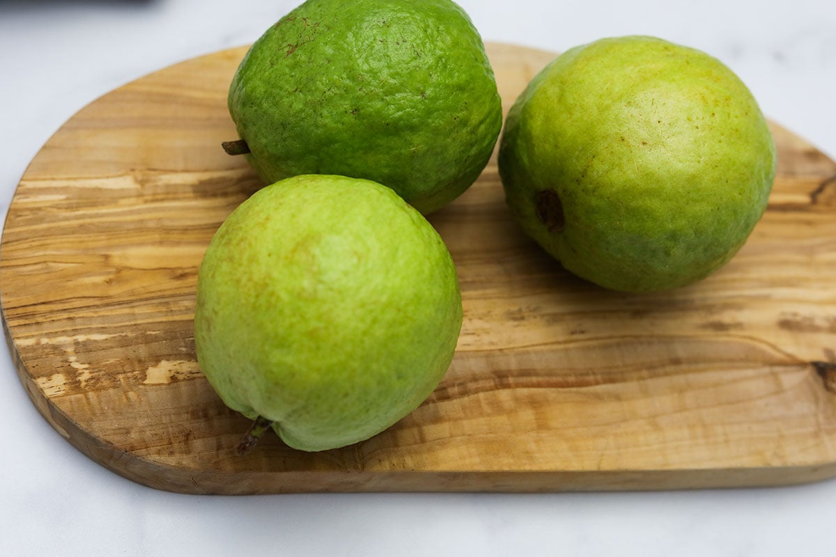 whole guava fruits on a cutting board